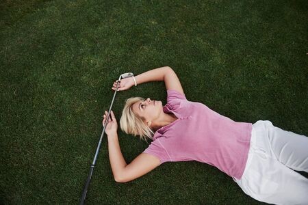 The girl lies on the golf course and relaxes after the game.