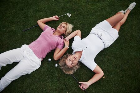 Two girls sisters lie on the golf course and relax after the game.