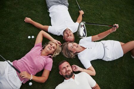 Four people, two guys and two girls, lie on the golf course and relax after the game.