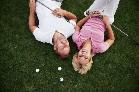 A couple, husband and wife lie on the golf course and relax after the game. Reklamní fotografie