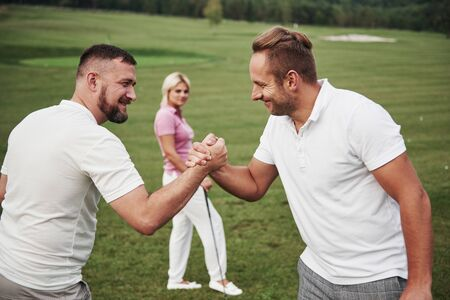 Three players play on the golf course. The team congratulates and shakes hands with each other.