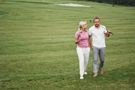 Sportive couple playing golf on a golf course, they stand to the next hole. Stockfoto