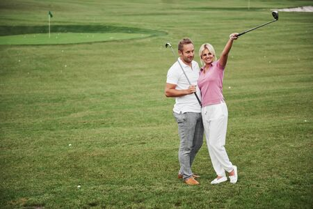 Sportive couple playing golf on a golf course, they stand to the next hole.