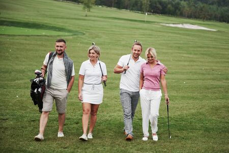 Group of stylish friends on the golf course learn to play a new game. The team is going to rest after the match. Reklamní fotografie