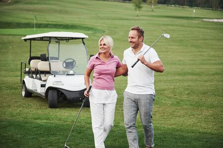 Two professional golfers, a woman and a man go together to the next hole. Lovers hug and smile, they have a date.