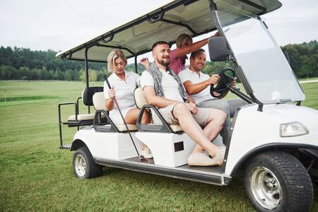 Young couples getting ready to play. A group of smiling friends came to the hole on a golf cart.