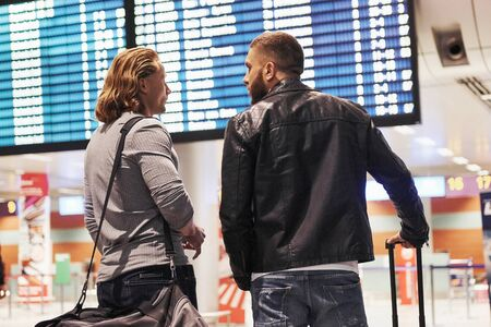 Photo of two comrades situating in airport near flight information display system.
