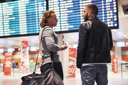 Discussion about planning a trip. Photo of two comrades situating in airport near flight information display system. Фото со стока