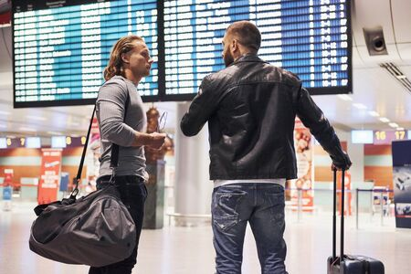 Conversation before departure. Photo of two comrades situating in airport near flight information display system.