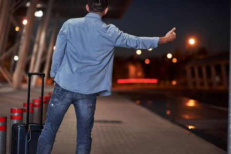 Short-haired man in jeans and a shirt with a baggage tries to catch the car.