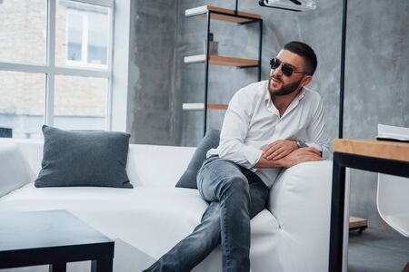 Young short-haired man in sunglasses sitting on couch in the office. Stock Photo