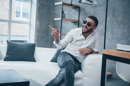 Smiles and shows an index finger. Young short-haired man in sunglasses sitting on couch in the office. Banco de Imagens