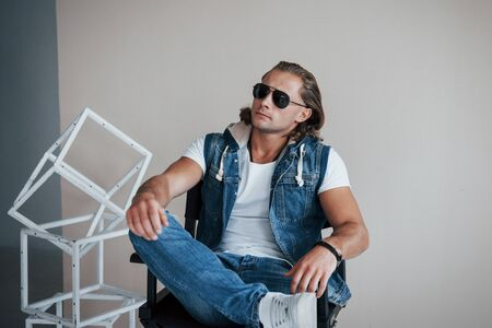 Thoughtful look. Portrait of young fashionable man with sunglasses on grey background.