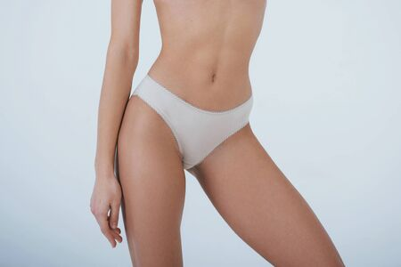 Close up photo of beautiful slim woman body in white underwear in the studio.