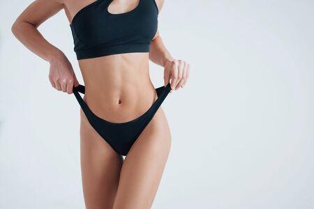 Tighten up. Womans body in white underwear on the white background. Standard-Bild - 134541514