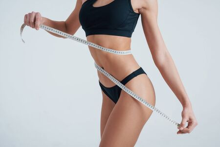 Female body with centimeter tape around on white background.
