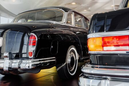 Back and side view of a black retro business class car with right backlight, chrome bumper and wheel disc, whitewall tire with the blurred left taillight of another dark old vehicle.