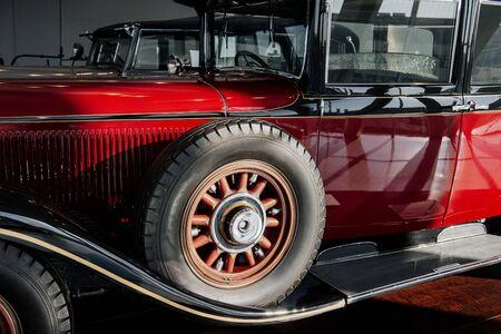 Profilansicht eines rot-schwarzen Retro-Autos mit Rechtslenker, Reserverad und Bogen darüber, Holzelemente in Scheibe, vertikale Scheibenwischer, Chrom-Sidestep.