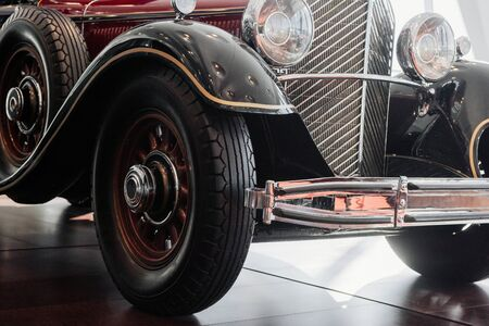 Schließen Sie die Vorder- und Seitenansicht eines roten Retro-Autos mit Chromscheinwerfer, Stoßstange und Kühler, schmalen Rädern mit einem Bogen darüber, einem Ersatzreifen und Holzelementen in der Scheibe.