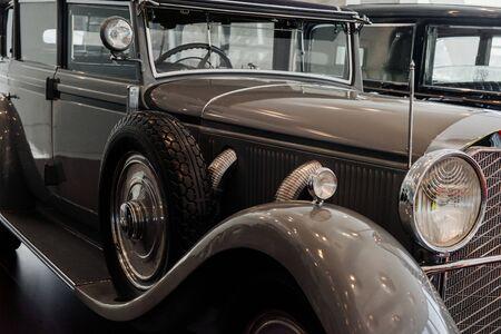 Seitenansicht eines grauen Retro-Autos mit Ersatzreifen und Bogen über dem Rad, verchromten vertikalen Scheibenwischern, Scheinwerfer, Scheibe, äußerem Auspuffkrümmer, Seitentritt.