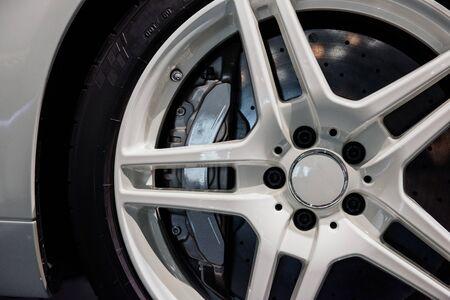 Nahaufnahme von weißen Leichtmetallrädern mit Bremsscheibenbelag, Niederquerschnittsreifen eines modernen Sportwagens.