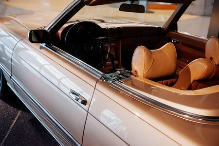 Side, close up view of beige retro cabriolet car leather interior and hood: steering wheel, dashboard, rear mirror and windshield. 版權商用圖片