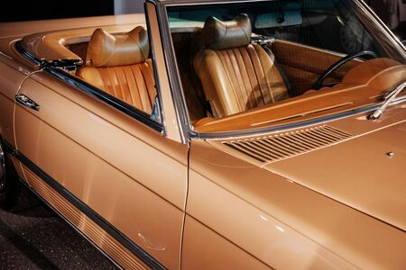 Side and front, close up view of beige retro cabriolet car leather interior and hood: steering wheel, rear mirror and windshield.