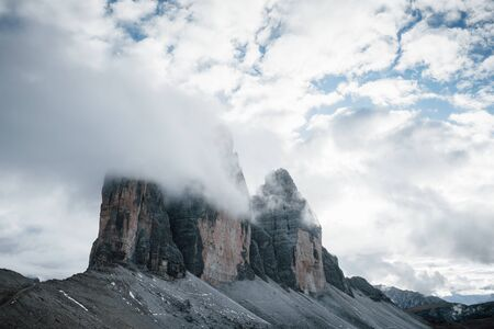 Little pieces of snow on the rocks. Mountains in the fog and clouds. Tre Cime di Lavaredo.