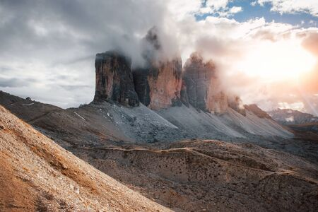 With sunlights new day has come. Mountains in the fog and clouds. Tre Cime di Lavaredo.