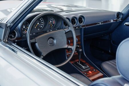 A side, close up view of dark gray retro car interior: steering wheel, automatic old gearbox, dashboard with wooden elements.