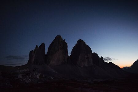 Night time landscape photo. Tre Cime mountains with three peaks. Two tourists working with camera far away on the left.