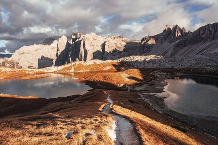 The path between two little lakes going to the great dolomite mountains standing at sunlight.