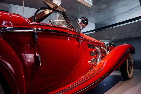 Flugzeug hängt am Hintergrund. Detailliertes fokussiertes Foto des fantastischen historischen roten Autos mit Scheinwerfer und Seitenspiegel. Standard-Bild