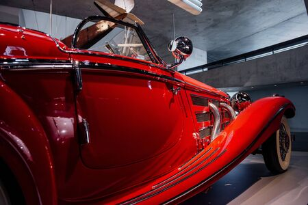 Plane hanging on background. Detailed focused photo of the awesome historical red car with a headlight and side mirror.