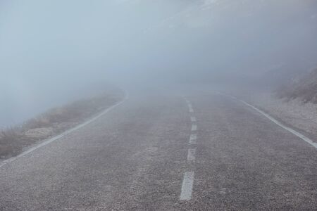 Mysterious looking road in the heavy fog near the mountains.