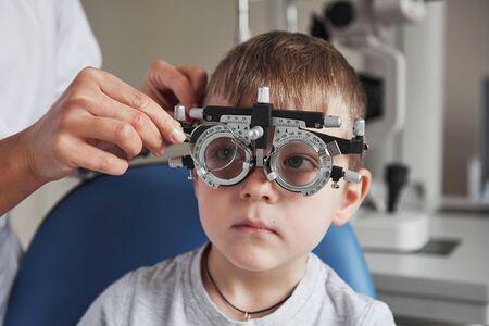 Kleiner Junge mit Phoropter, der seine Augen in der Arztpraxis testet.