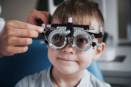 Tuning the intrument. Little boy with phoropter having testing his eyes in the doctors office. Foto de archivo