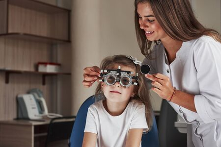 Looking at board. Little girl in glasses sitting in clinic and having her eyes tested. Banque d'images