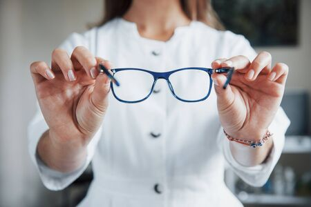 Female doctor showing the blue glasses by holding it in two hands. 版權商用圖片 - 134545056