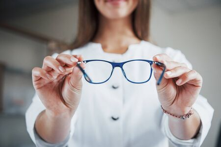 Front view. Female doctor showing the blue glasses by holding it in two hands.