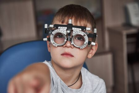 Shows an index finger. Close up portrait of child in special glasses.