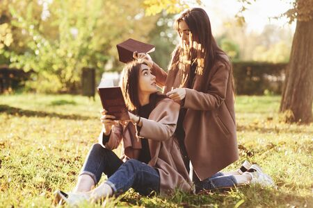 Brunette twin girls sitting on the grass with brown books in hands and looking at each other, when one of them is standing on her knees near the back of her sister in autumn park on blurry background. Banque d'images