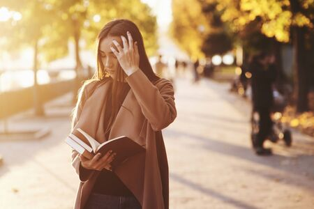 Young pretty brunette girl reading a brown book, fixes her hair with the left hand, while standing in autumn park in casual coat with trees at the blurry background and copy space. Banco de Imagens