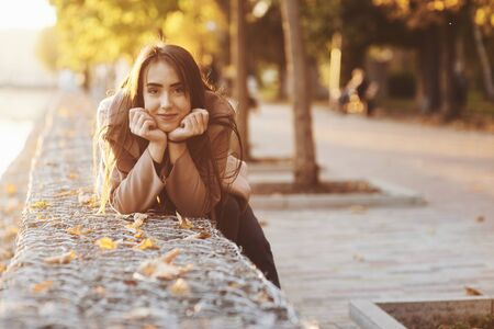 Young, pretty brunette girl leaned on the wall with her two hands under the chin, wearing casual coat with an autumn sunny park on the blurry background with a copy space.