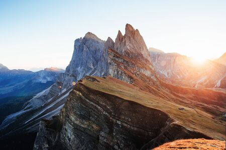 Variety of blue and yellow colors. Beautiful sunset in the Italian majestic Seceda dolomite mountains. Banco de Imagens
