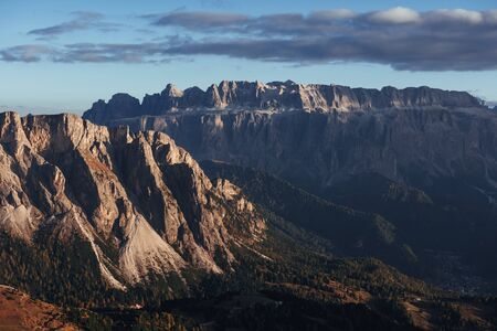 Sun began to hide. Landscape of mountains and trees below at sunny day. Italian Seceda alpes.