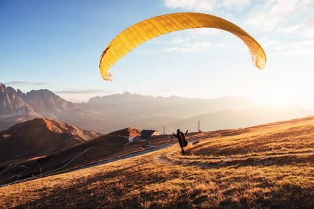 Paraglider run and accelerates himself to take off from the mountain of Seceda.
