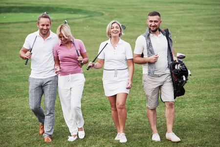 Cheerful friends spending time in the golf field with sticks and good mood.