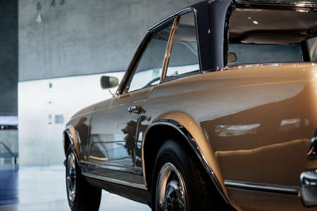 Gorgeous shiny piece of vintage art. Photo of brown vintage polished and shiny car parked indoors.