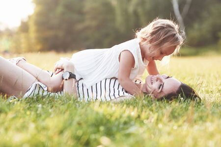Lie down on the grass. Lovely portrait of girl and her daughter hug each other outside.